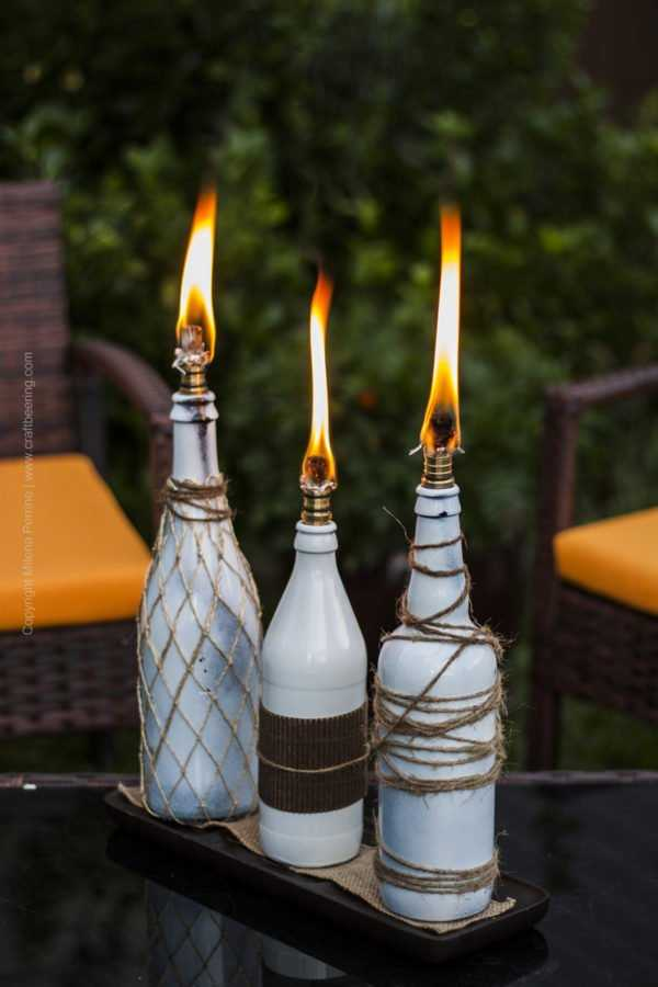 Beer bottle tiki torches on coffee table. Ambiance creators and mosquito repellent in one