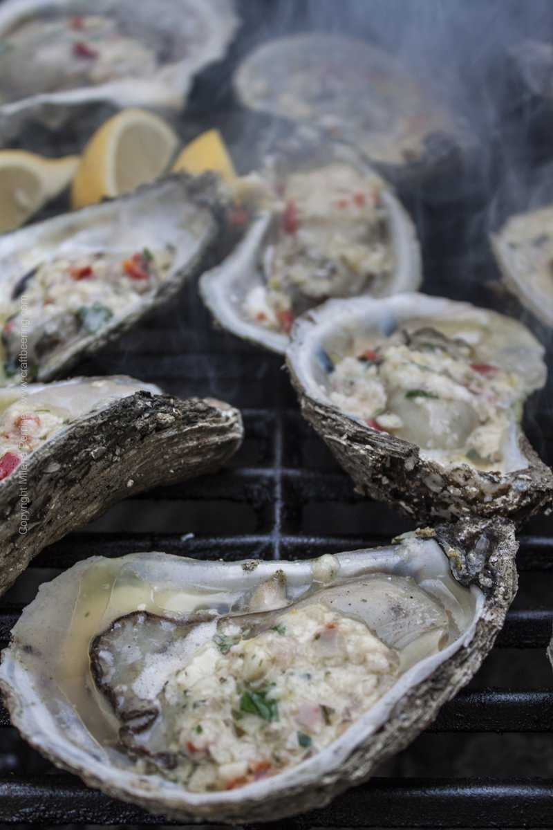 Smoking chargrilled oysters on the half shell with a butter compound.