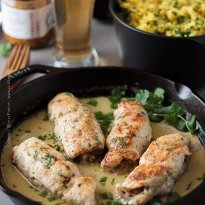 Beer chicken roulades in cast iron skillet, stuffed with curry garlic and onions and simmered in a delicious sauce of Witbier and coconut milk. #cookingwithbier #chickenroulades #chickenrecipe #beerchicken #currygarlic