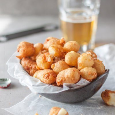 Fried cheese curds! Our recipe encases them in a crispy, light beer batter | A bowl full of delicious, golden beer battered fried cheese curds is exactly what your cold beer needs:) #cheesecurds #friedcheesecurds #beerbattered #appetizer #gamedayfood #beergardenfood #friedcheese