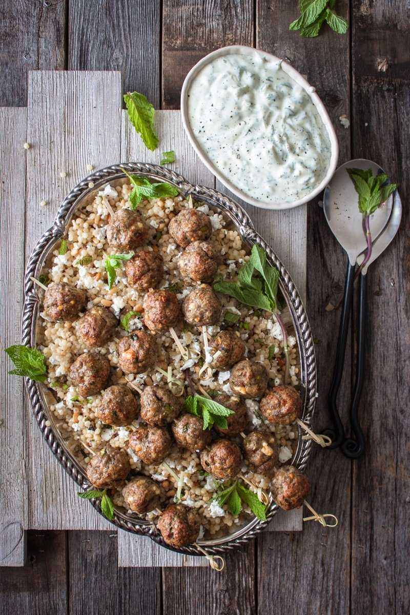 Lamb meatballs with feta, cumin and a touch of Pilsner. Served over pine nuts couscous with mint and feta and with an amazing yogurt garlic dill dip. #lambmeatballs #lamb #lambrecipe #lambskewers