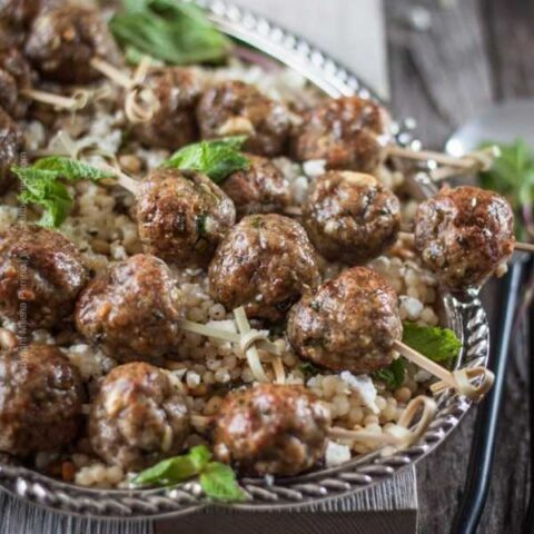 Lamb meatballs with feta, cumin and Pilsner served over a platter of buttery couscous with pine nuts, feta and mint. Lamb recipe heaven! #lambmeatballs #lambrecipe #cumin #lambrecipe