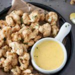 Best fried cauliflower bites ever. Light crunchy batter flavored with red pepper flakes (optional) and served with curry garlic lime aioli. Superb! #friedcauliflower #beerbattered