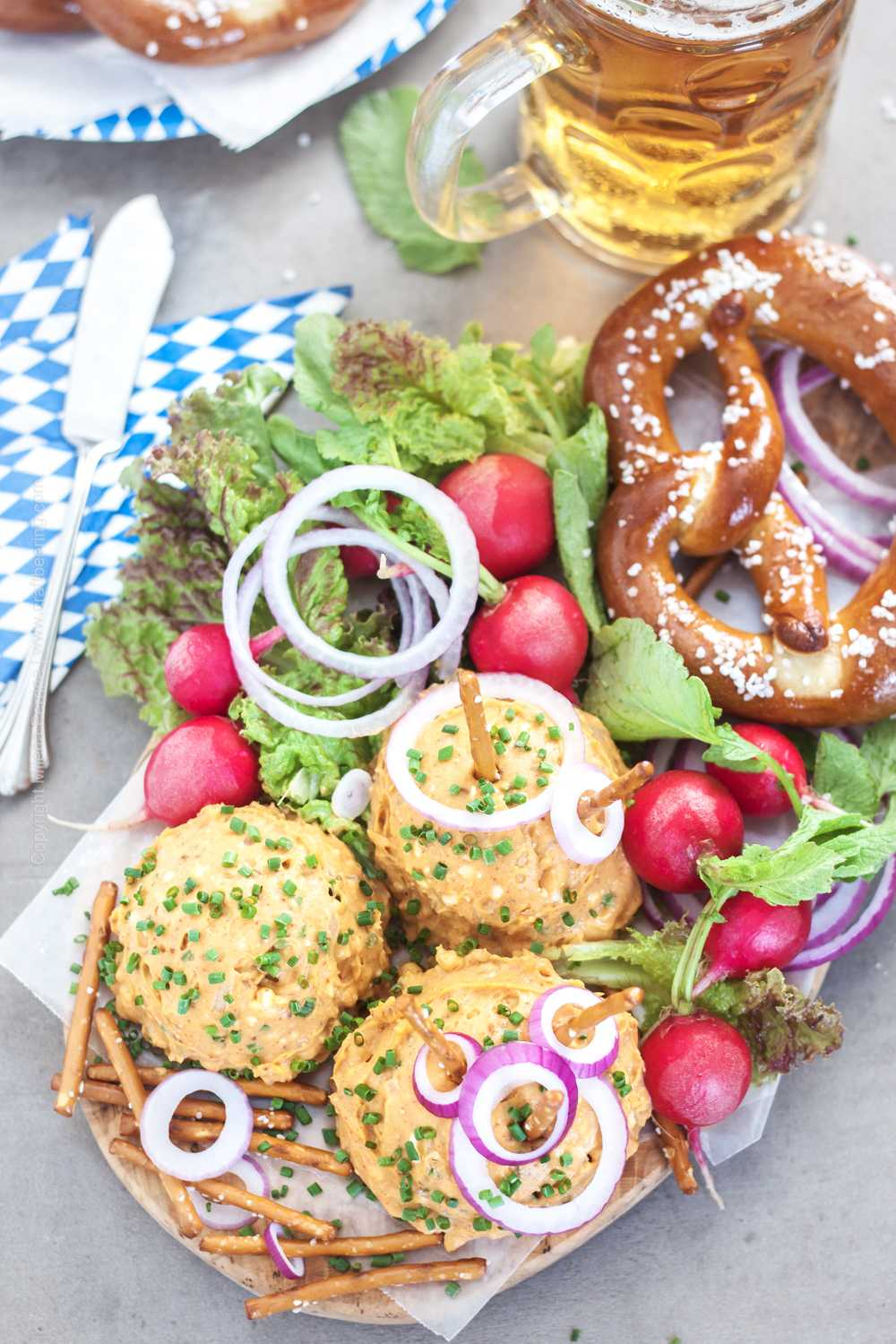 Obatzda cheese dip - traditional Bavarian presentation with onions, radishes, lettuce.