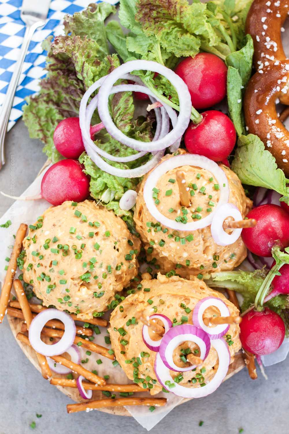 Hofbrauhaus beer cheese recipe. Presentation of obazda dip with fresh veggies and soft pretzels.