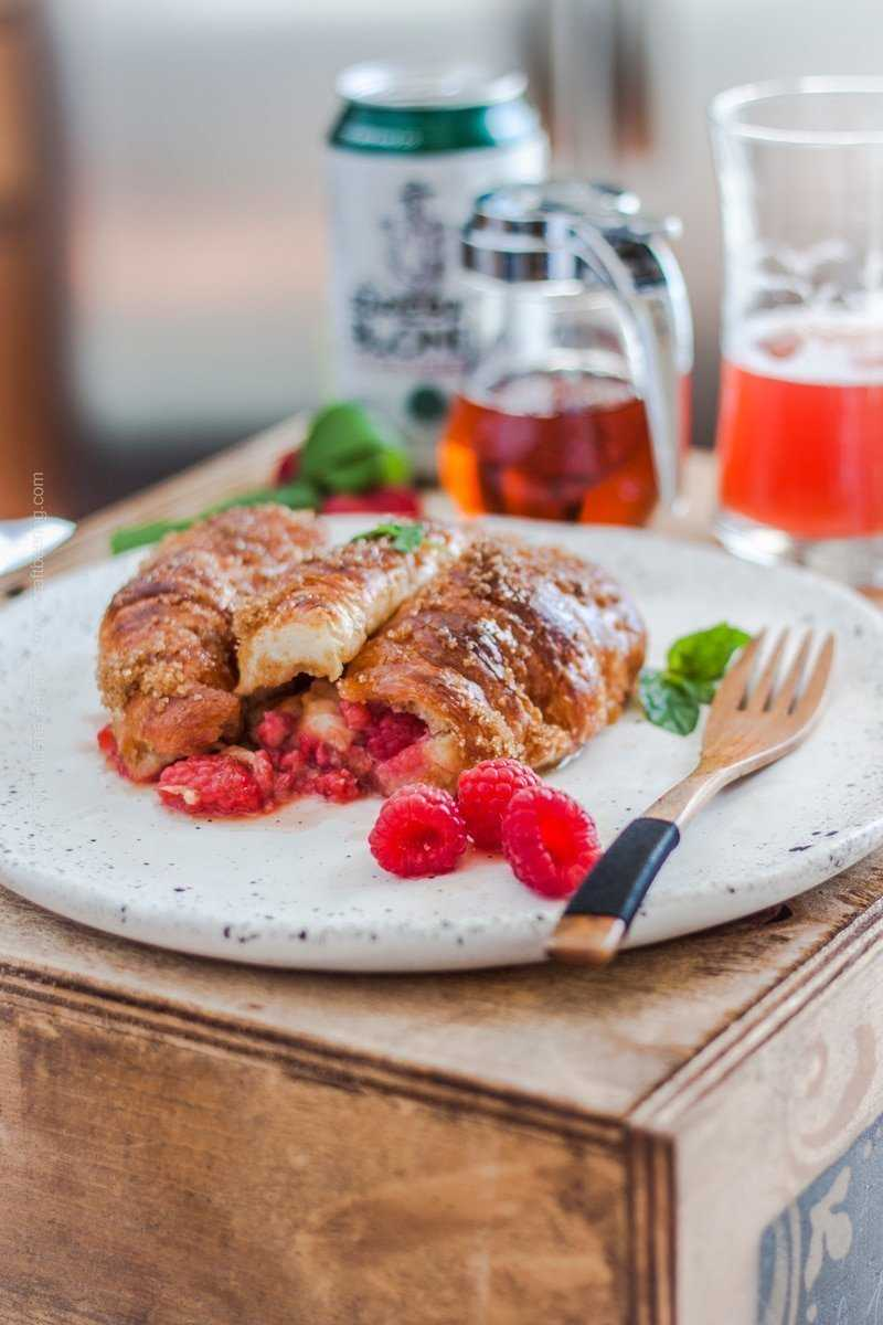 Croissant French toast stuffed with raspberries and served topped with raspberries and drizzled with maple syrup.