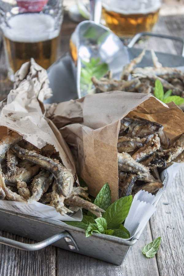 Fried anchovies served in paper bags. Crispy, salty bites of perfection. Pair with a cold lager.