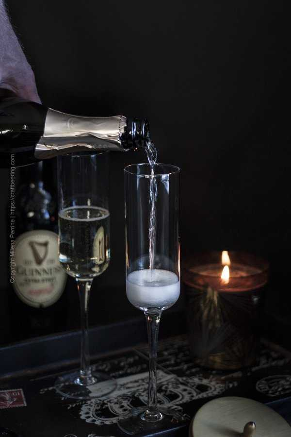 Sparkling wine poured in a flute for Black Velvet drink.