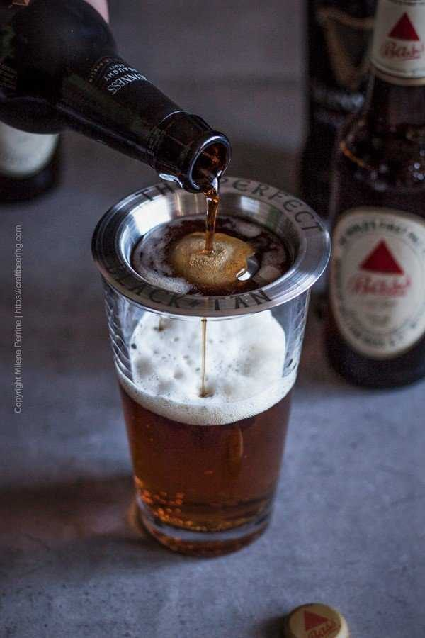Guinness being poured over Bass ale using a layering tool.