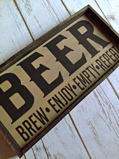 Brew, enjoy, empty, repeat rustic beer sign.