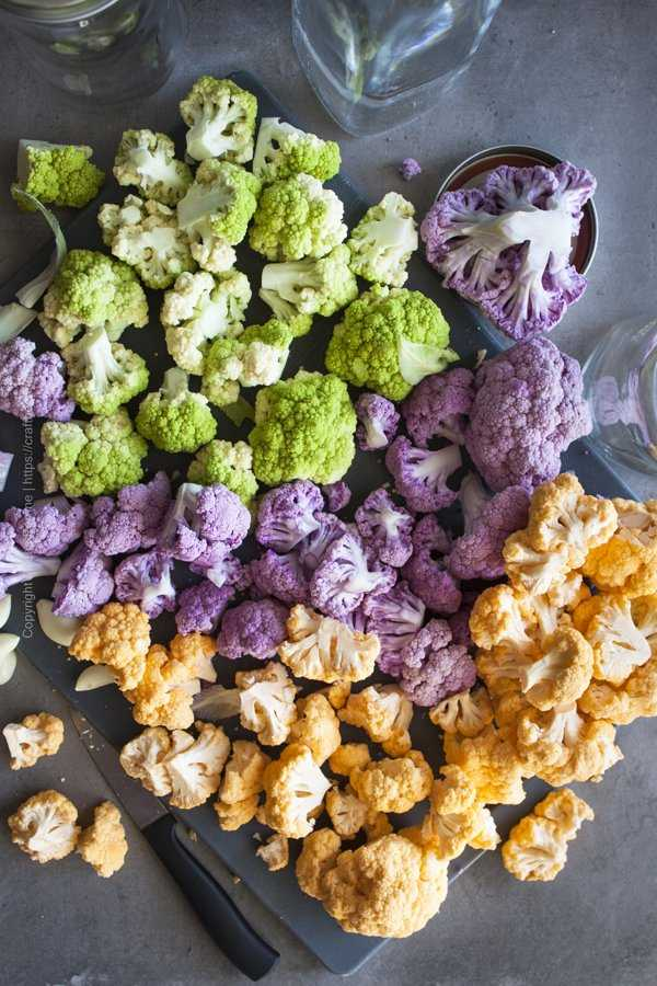 Tri color cauliflower florets scattered over a cutting board.