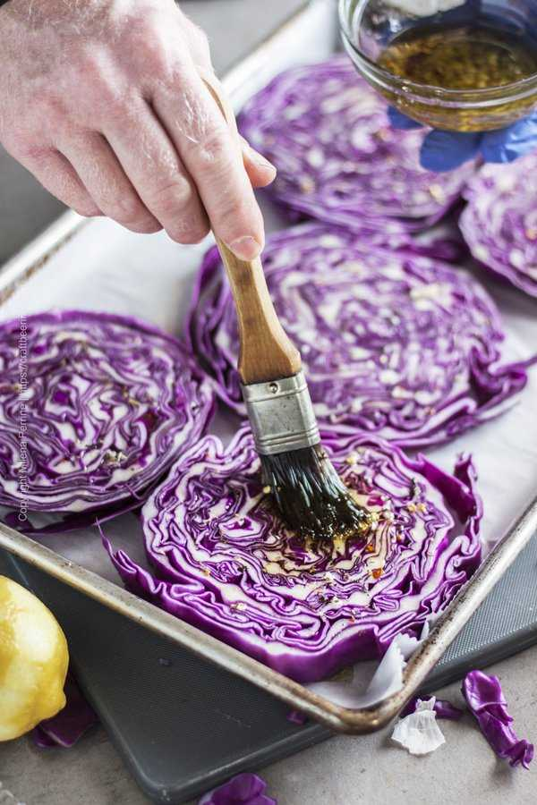 Brushing seasoned oil over cabbage steaks.