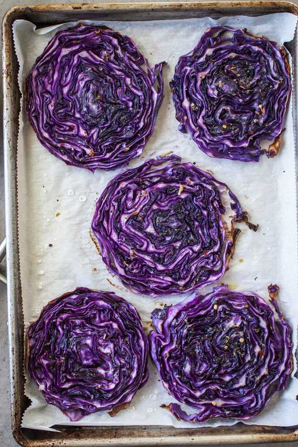 Baking sheet with roasted cabbage steaks just out of the oven.