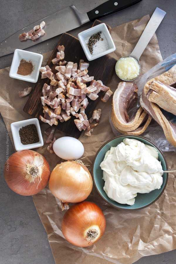 Topping ingredients for tarte flambee - smoked bacon, onions, creme fraiche, clarified butter, egg yolk, nutmeg, salt and pepper, caraway seeds.