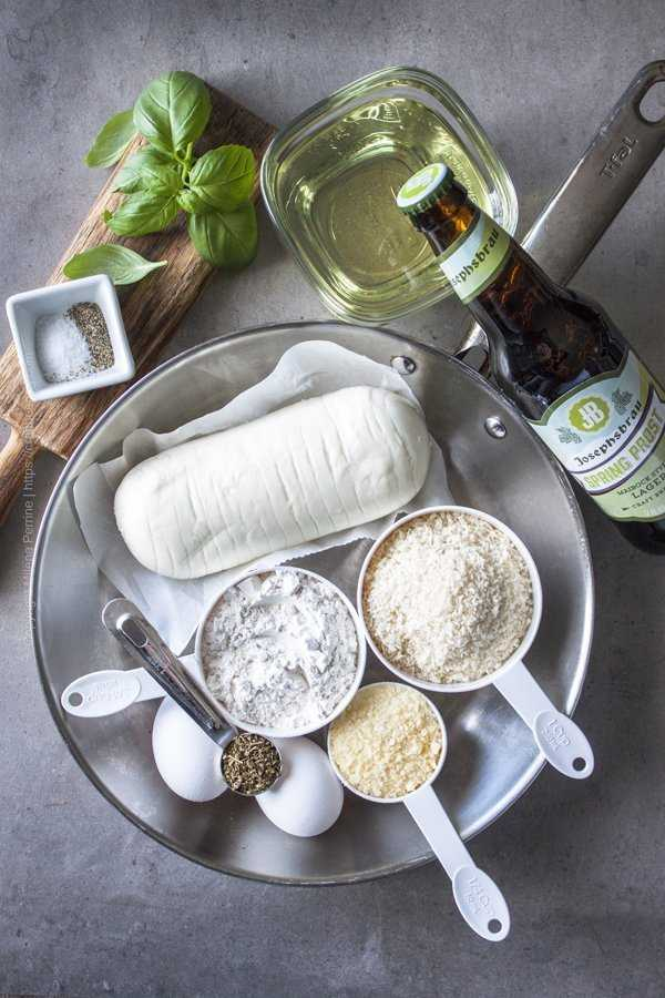 A frying pan and the few simple ingredients necessary for fried mozzarella - the cheese itself, bread crumbs, eggs, flour, oregano, parmesan.