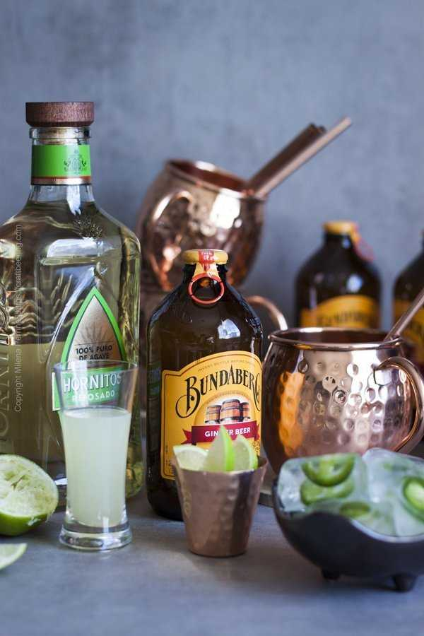 Ingredients for Mexican mule - tequila reposado, ginger beer, lime juice, lime wedges and jalapeno ice cubes.