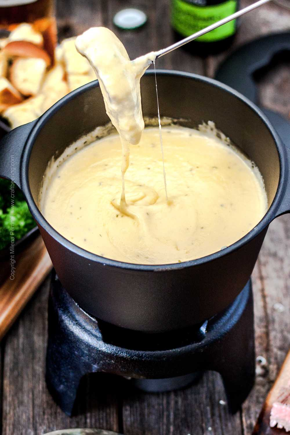 Steak and bread cube being dipped in beer cheese sauce in fondue pot