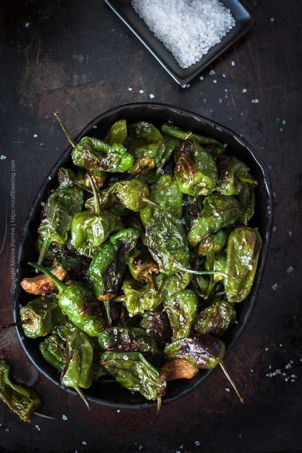 Traditional pimientos de Padron, served in a small dish, fried in olive oil, with blistered skins and sea salt flakes.