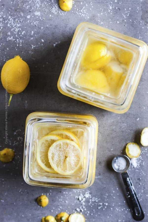View from above over jars with preserved lemons - one with whole quartered fruit and one with lemon slices.