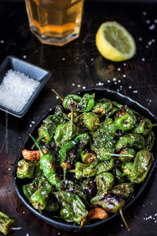 Padron peppers in a tapa dish with a glass of beer.