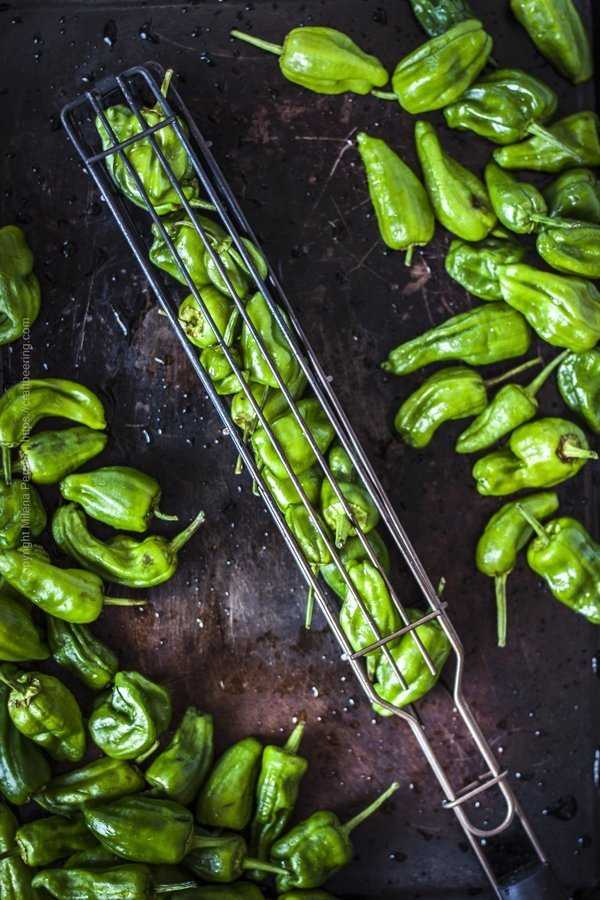 Pimientos de padron places inside a grill basket for easier handling over the grill