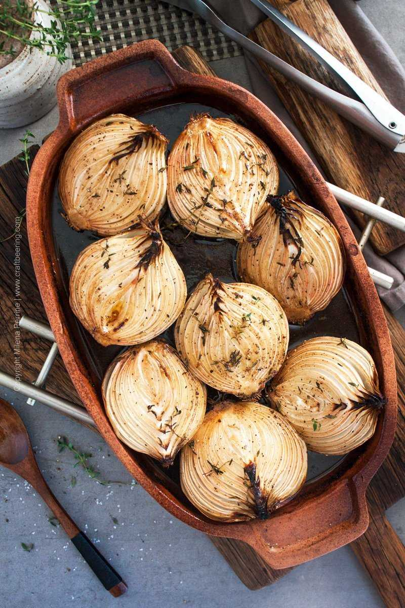 Slow roasted onions in terracotta dish.