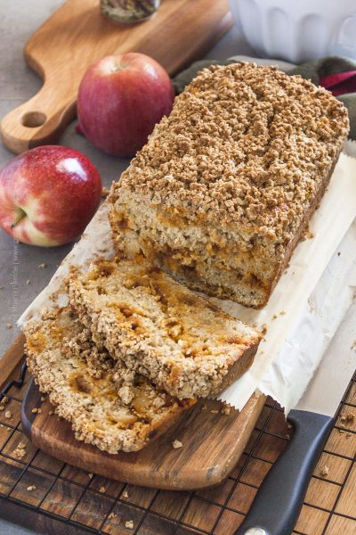 Streusel apple bread loaf with slices showing light texture dotted with caramel chips.
