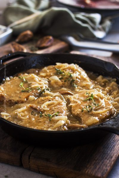 Braised pork loin chops plated family style and smothered in a rich gravy like sauce with onions, figs and Belgian ale.