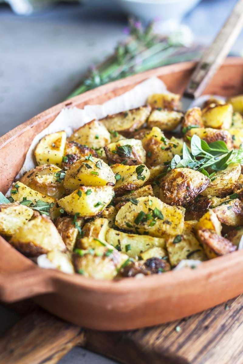 Close up of garlicky roasted potatoes served family style, garnished with fresh herb sprigs.