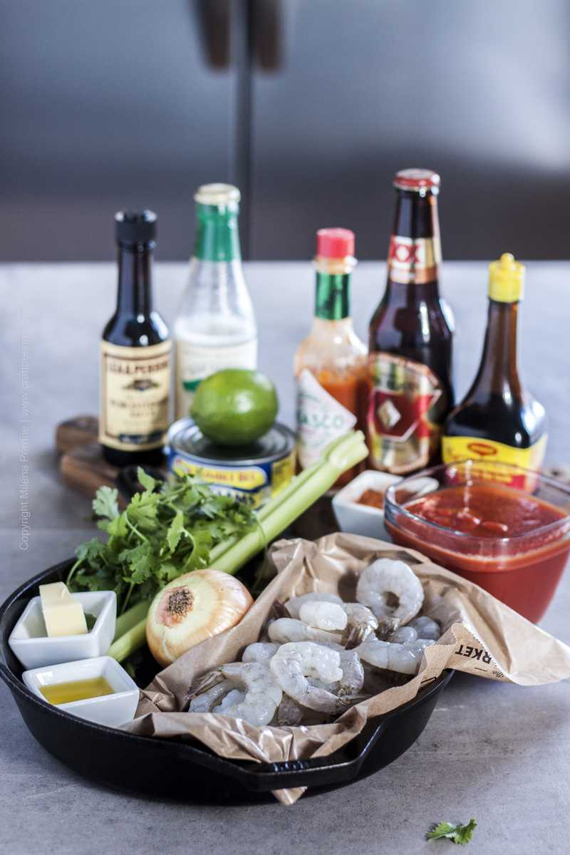 Line up of ingredients for spicy shrimp - clamato beer style. Raw shrimp, hot sauce, tomato sauce, dark lager, onion, celery, lime, clam juice, canned clams, magi sauce, Worcestershire, butter, olive oil, cilantro, chile lime seasoning.
