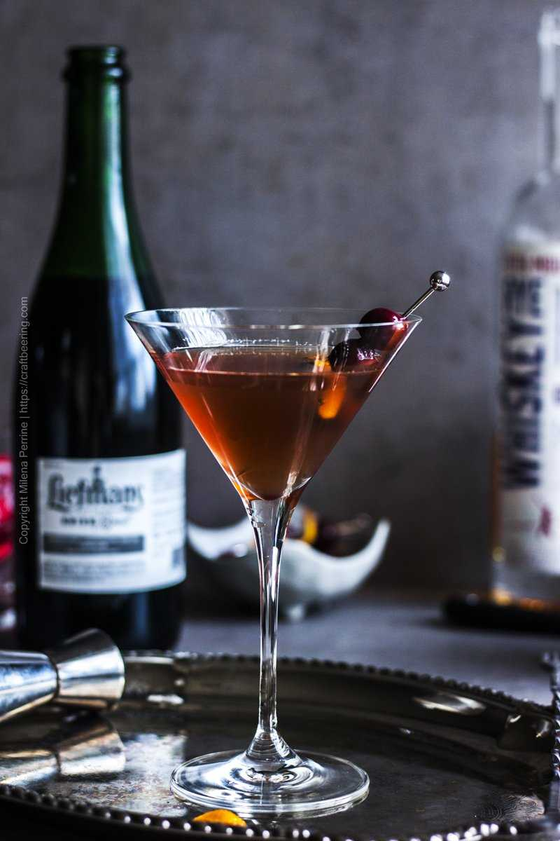 Manhattan cocktail in a high stemmed martini glass with skewered cherries and an orange twist.