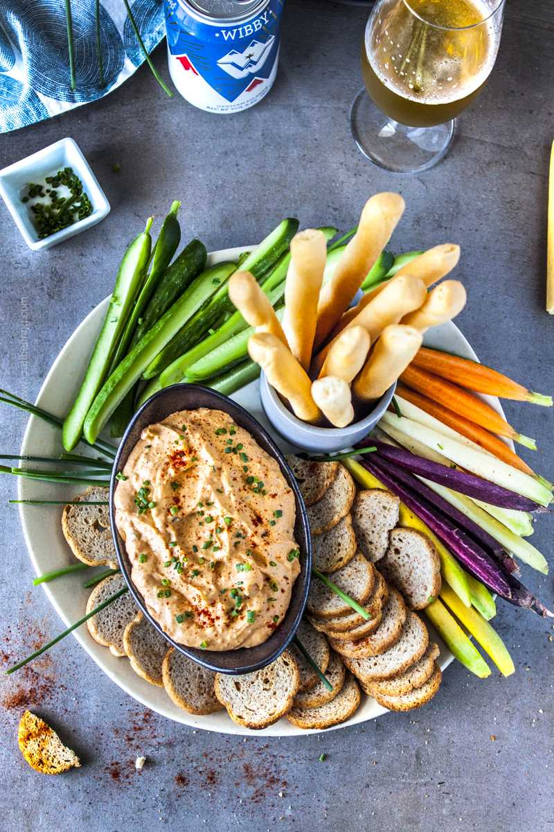 Pub cheese dip in the middle of a platter of crackers, bread sticks and veggie sticks.