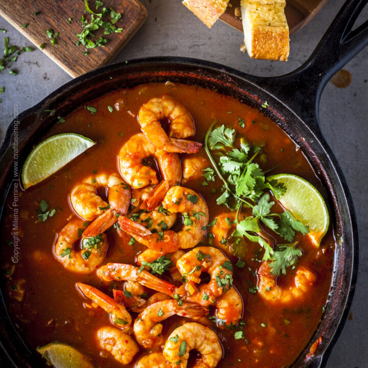 Skillet of spicy shrimp amidst plentiful clamato beer inspired tomato and dark lager sauce with zesty seasonings.