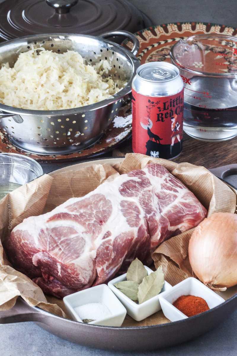 Raw ingredients needed for baked pork and sauerkraut- boneless pork shoulder, onion, bay leaf, paprika, olive oil, sauerkraut.