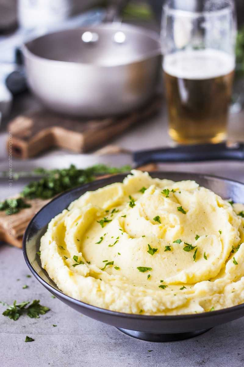 Beer mashed potatoes in a serving bowl, garnished with parsley.