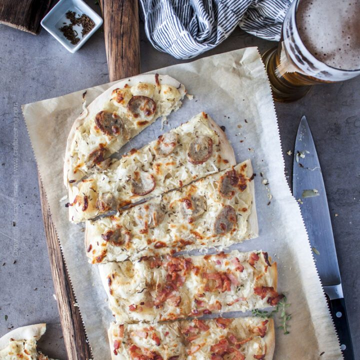 Sauerkraut pizzas with different toppings, sliced and served side by side on a rustic cutting board.