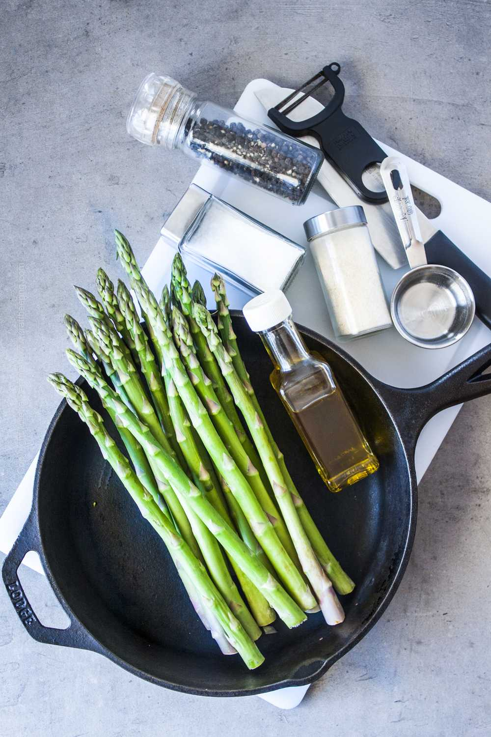 Ingredients for sauteed asparagus (cast iron skillet, asparagus spears, olive oil, water, seasonings.