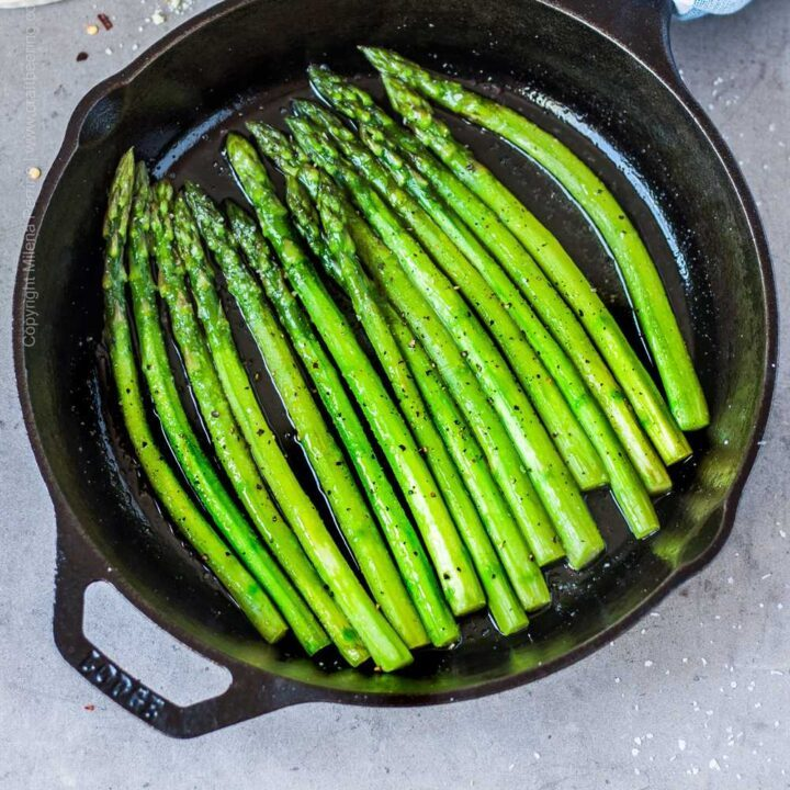 Cast iron skillet asparagus cooked to perfection in combination sear and steam method.