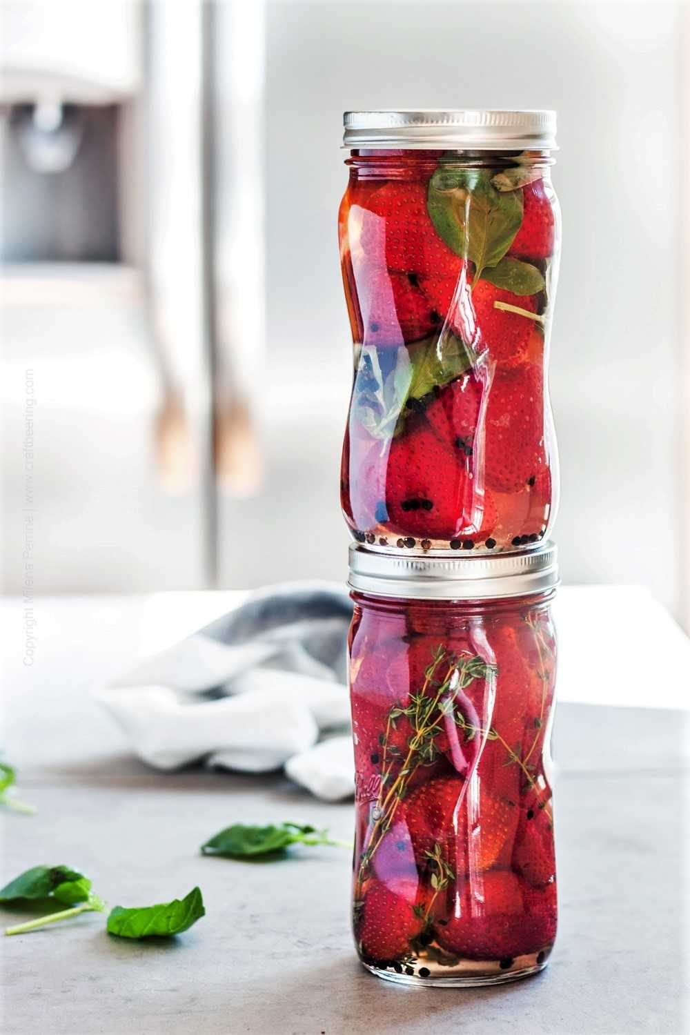 Stacked jars with strawberries in pickling liquid
