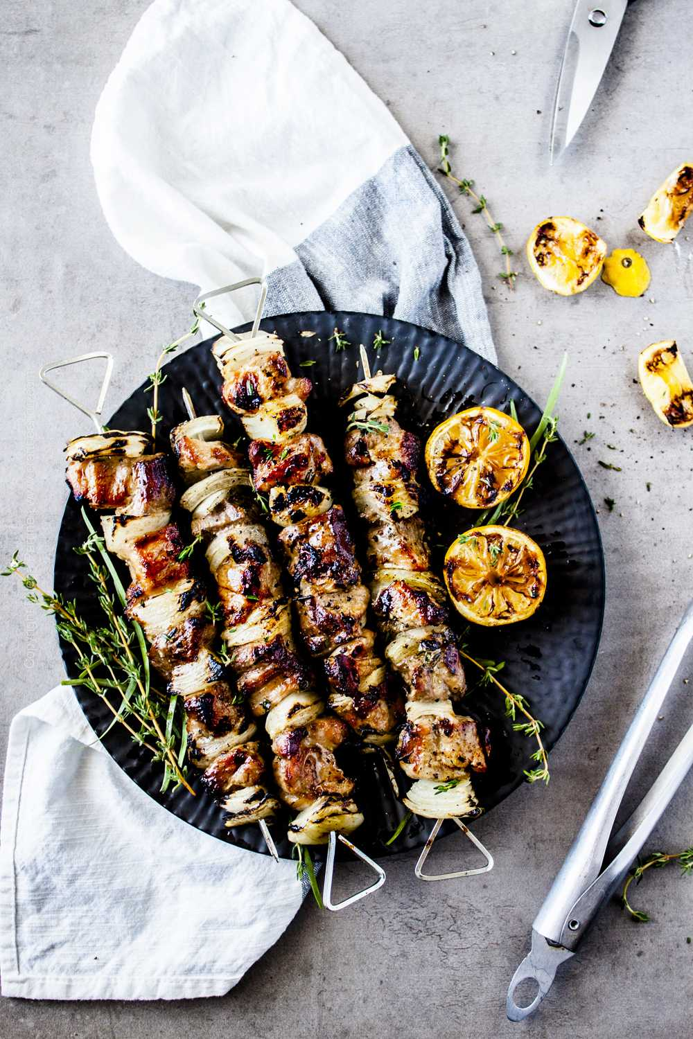 Pork skewers plated with fresh herbs and charred lemon halves.