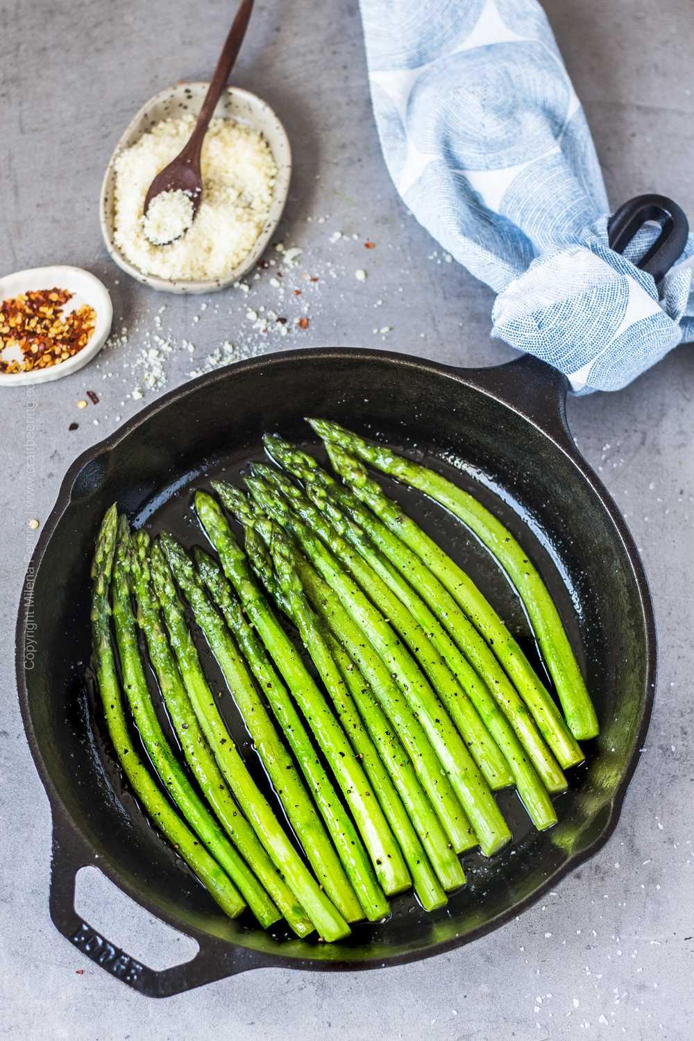 Cast iron skillet sauteed asparagus seasoned with Parmesan and red pepper flakes.