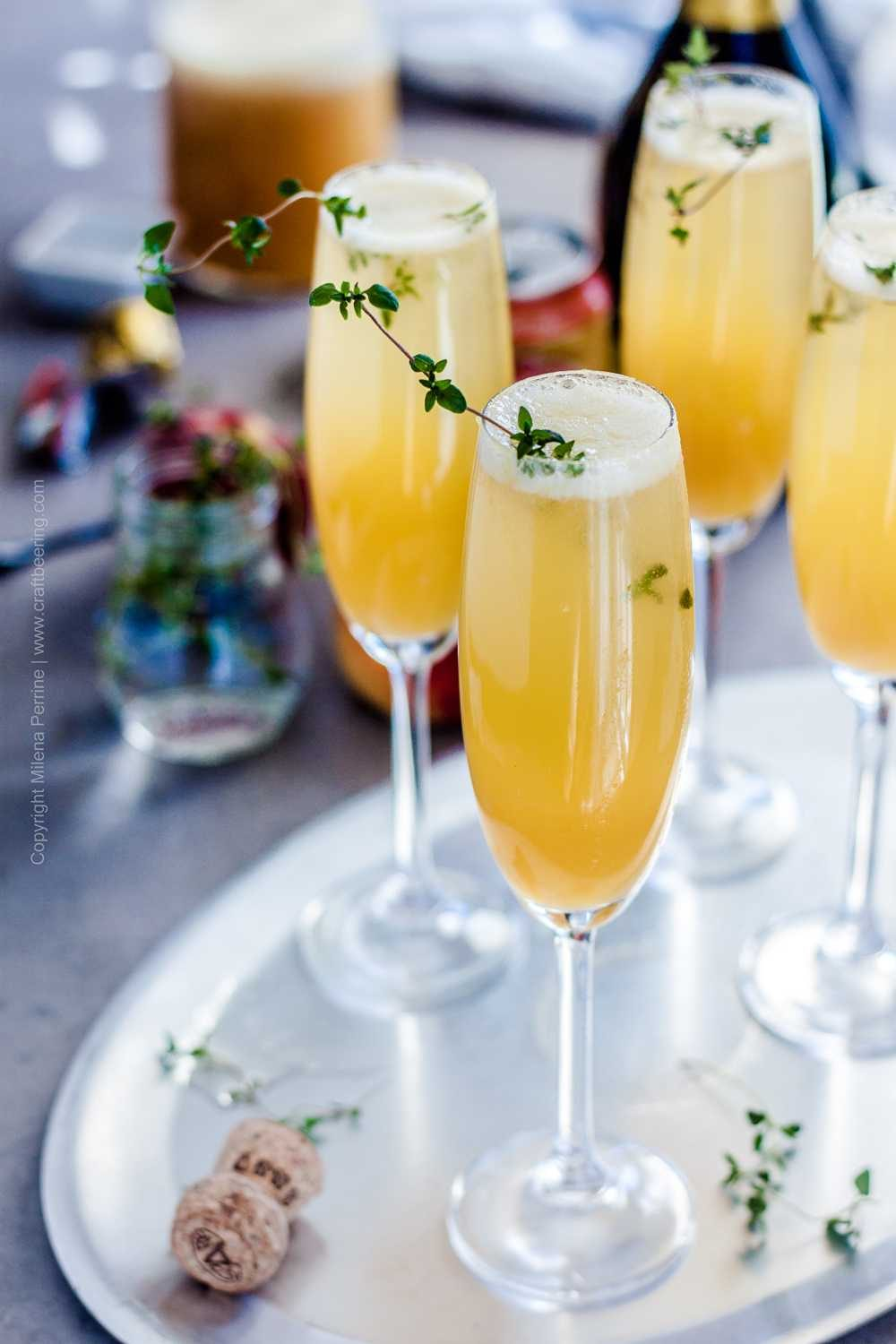 Fresh Peach Bellini Cocktail in flute glasses garnished with thyme