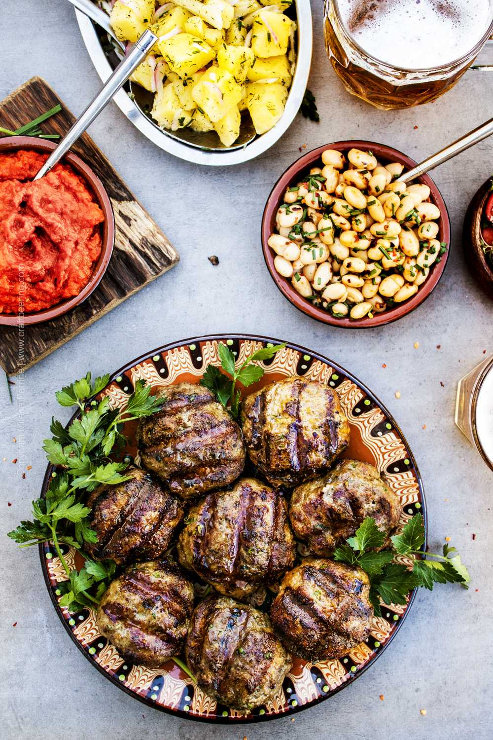 Grilled kafta served with traditional sides - luitenitsa, potato salad, bean salad and beer.