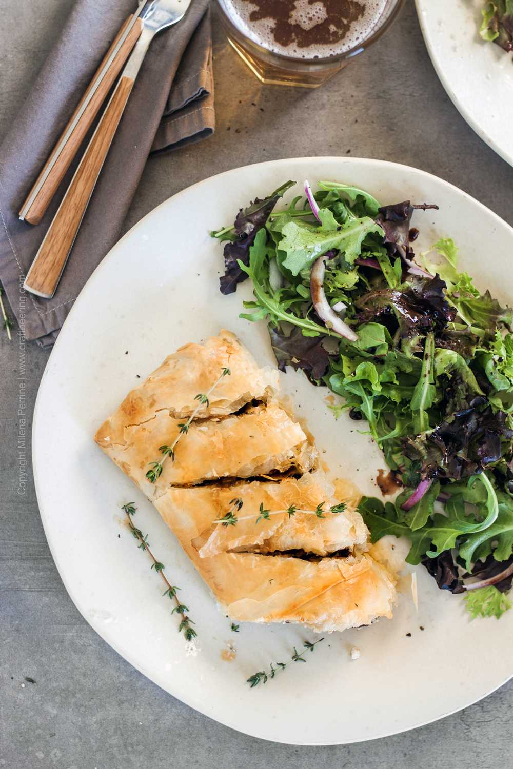 Plated mushroom strudel with mixed greens salad with balsamic.