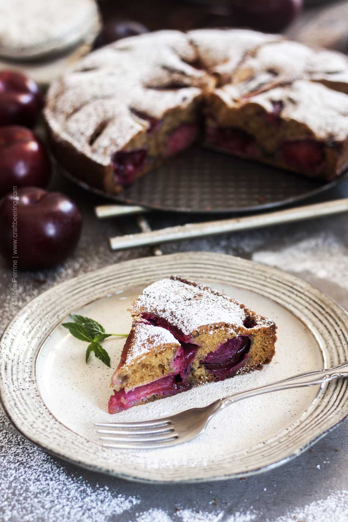 Austrian plum cake (or German Zwetschgenkuchen) a slice in front of the whole cake.