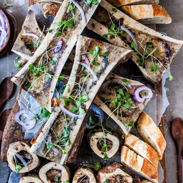 Roasted beef marrow bones - canoe cut and cross-cut served with shaved onions, micro greens and baguette.