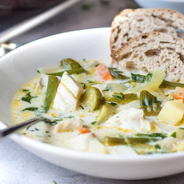 Cod fish stew with creamy broth and fresh herbs, served with rye sourdough bread.