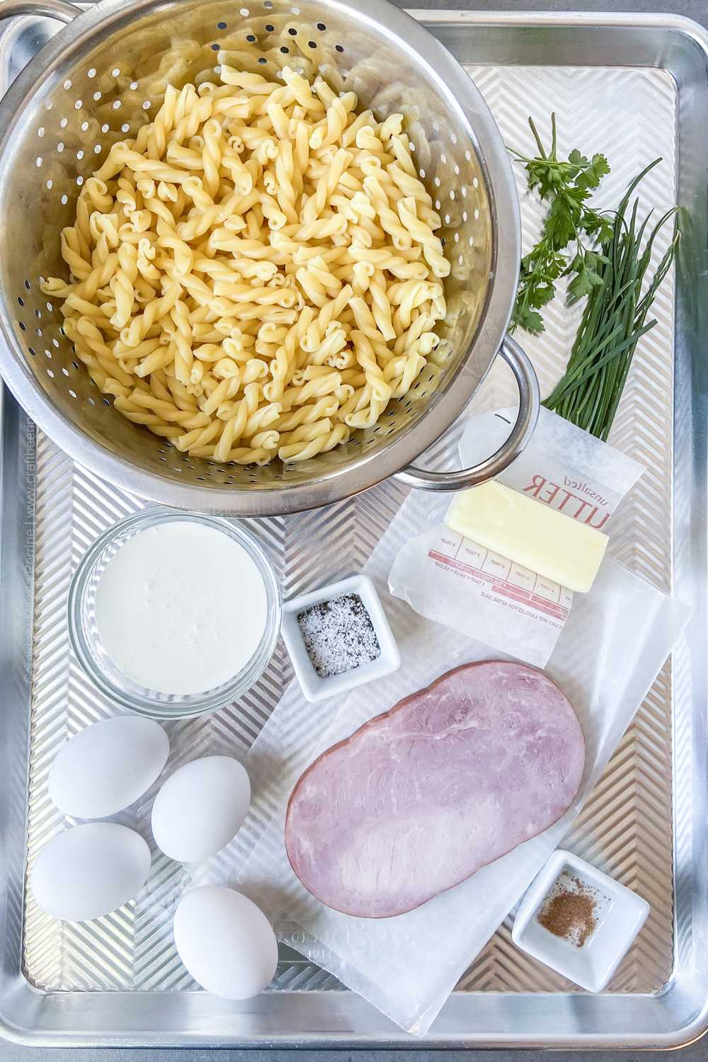 Cooked ham, al dente spiral pasta, heavy cream, eggs, butter, nutmeg, salt and pepper and chives and parsley.
