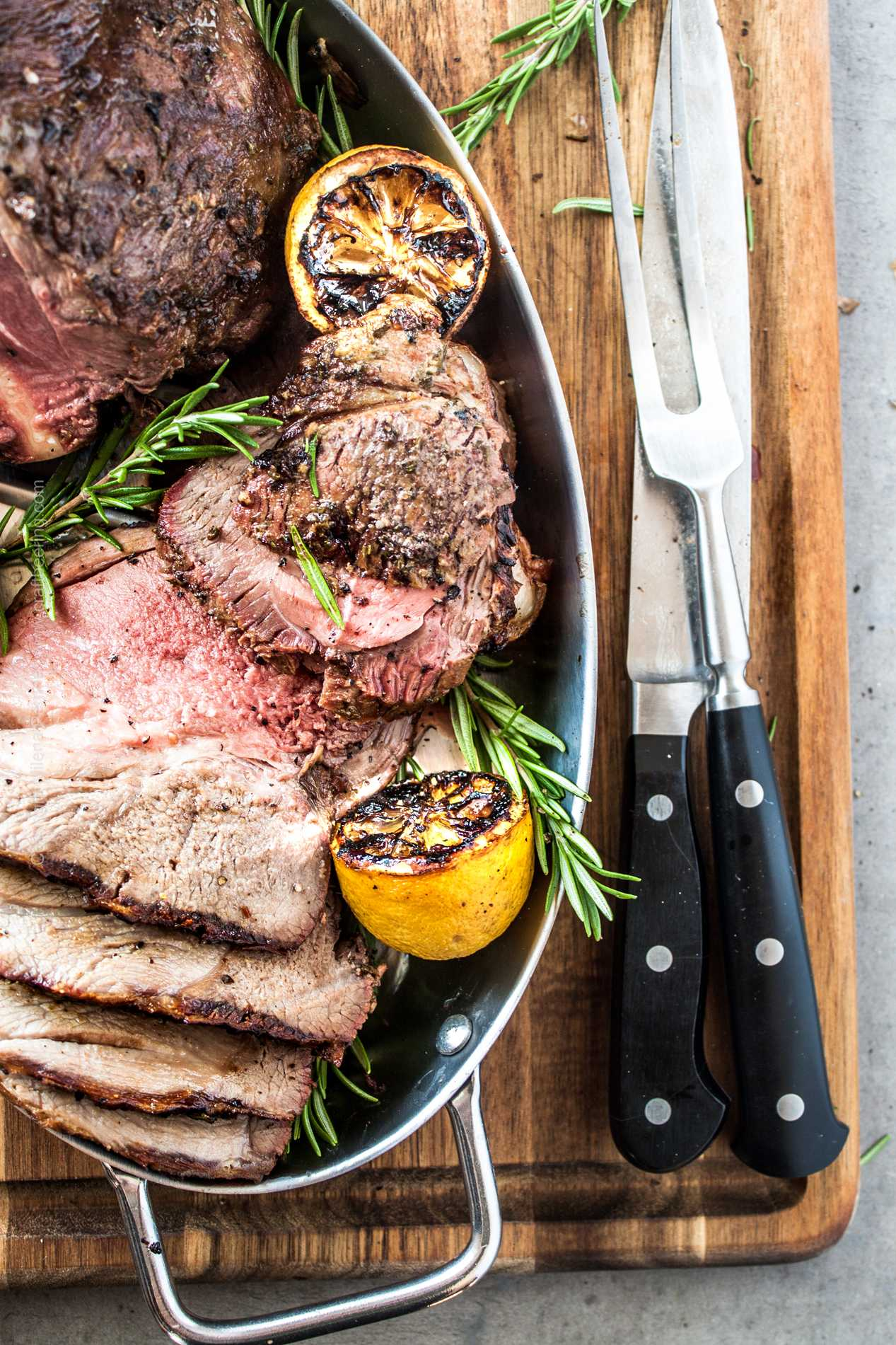 Juicy grilled leg of lamb garnished with rosemary, grilled lemons and garlic.