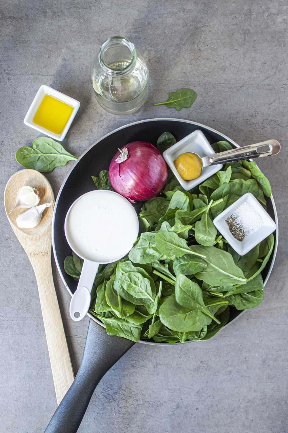 Heavy cream, spinach and other raw ingredients for spinach cream sauce.